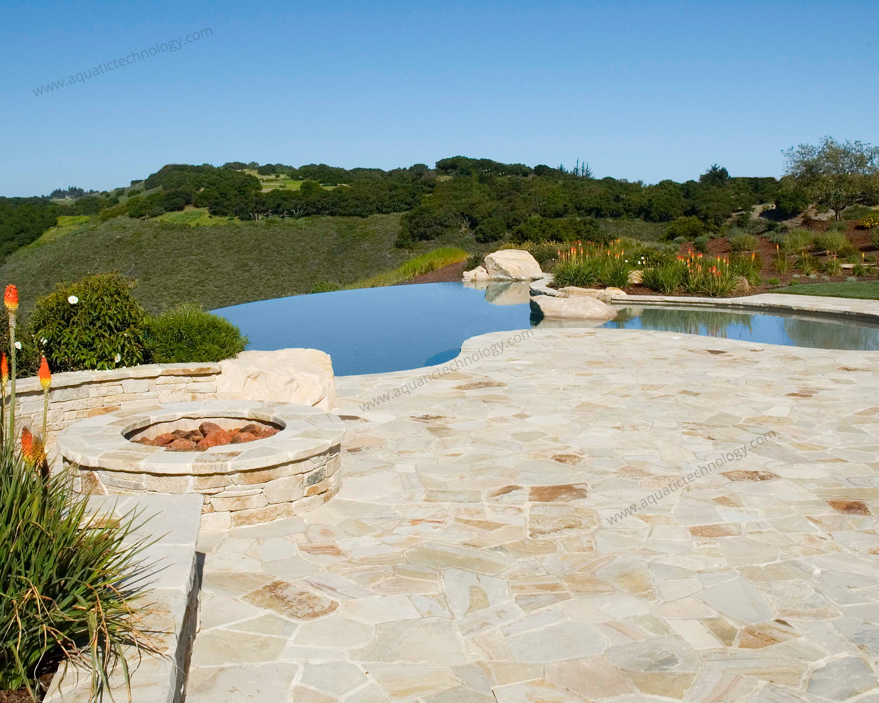 Infinity edge pool stone patio gas fire feature