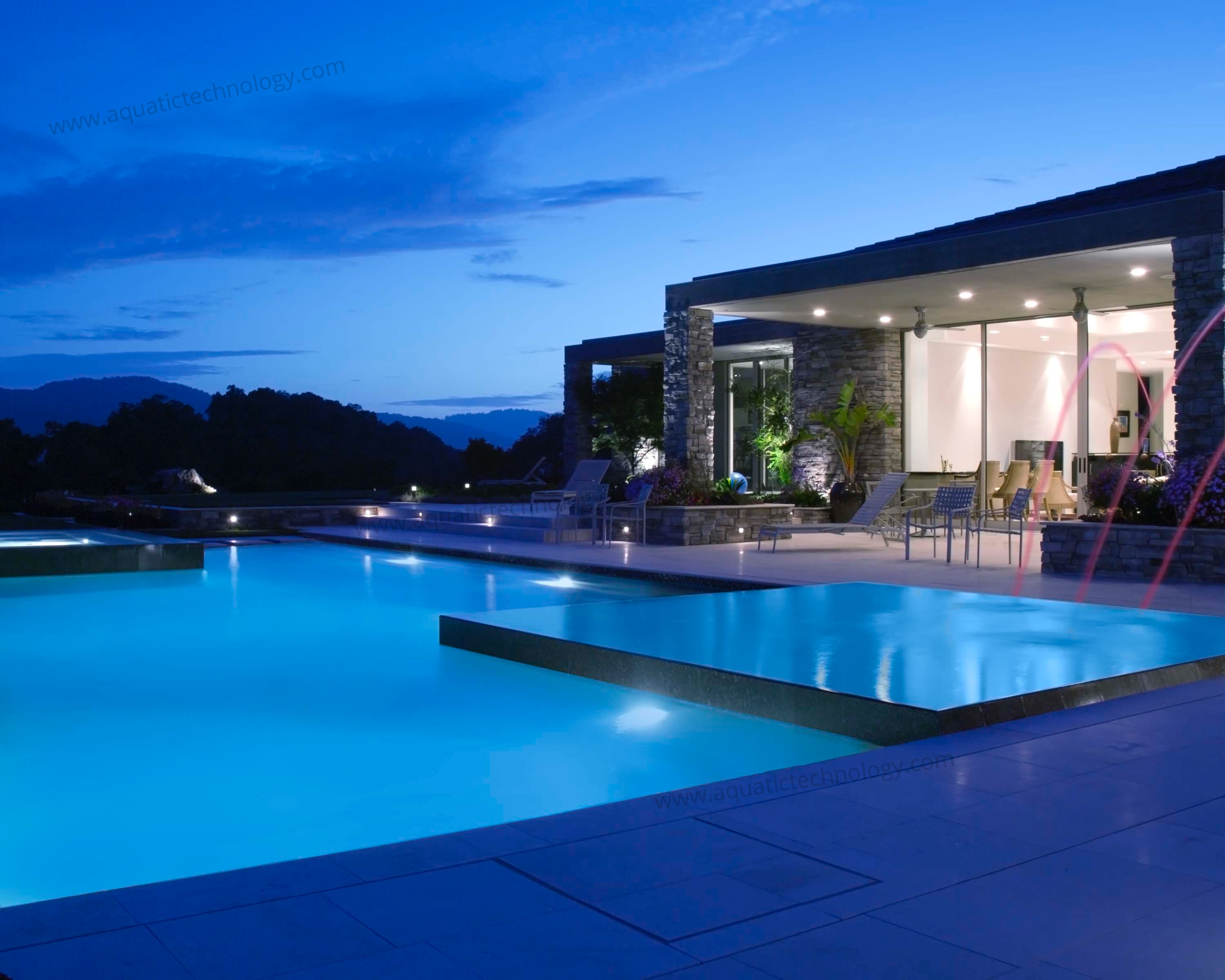 Nighttime infinity edge pool laminar fountains